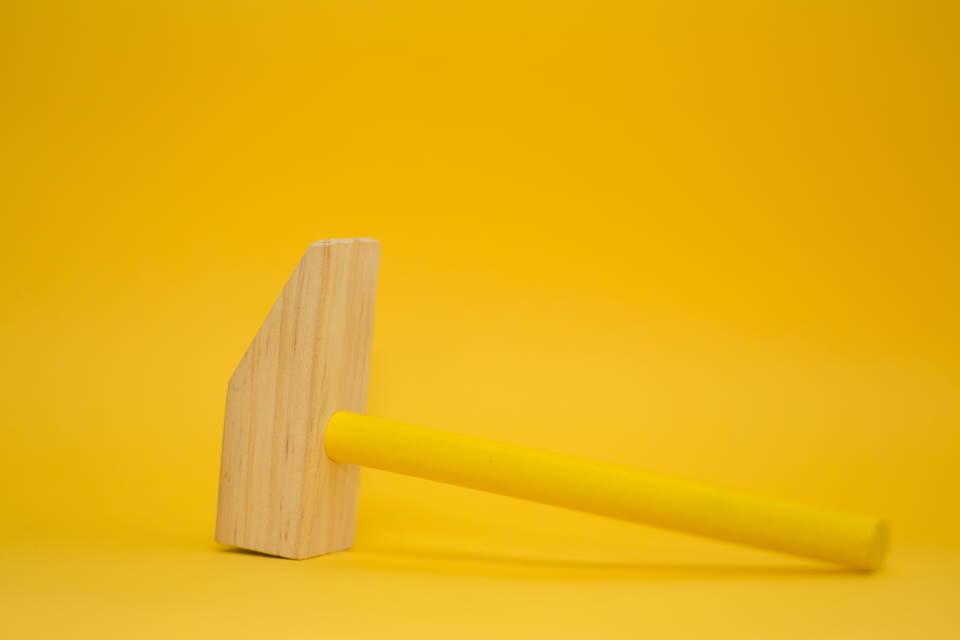 Holzhammer auf dem gelben Hintergrund
